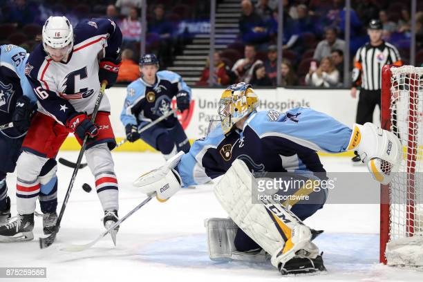 Cleveland Monsters right wing Miles Koules attempts to redirect the puck as Milwaukee Admirals goalie Juuse Saros swipes at the puck with his stick...