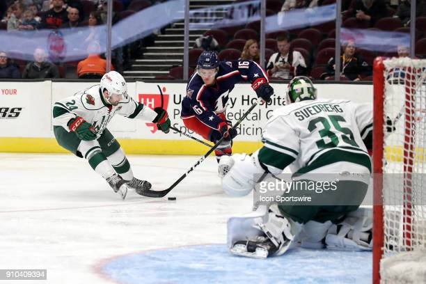 Cleveland Monsters right wing Miles Koules looks to shoot against Iowa Wild goalie Niklas Svedberg as Iowa Wild defenceman Ryan Murphy defends during...