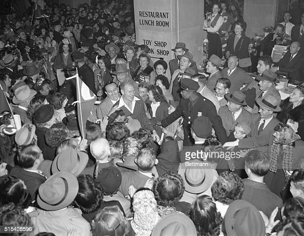 Bill Veeck leads Cleveland Indians through cheering fans after all night train ride from Boston Team arrived to play their World Series game here...