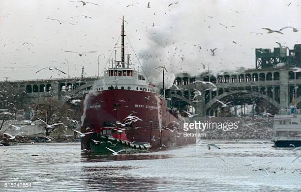 Gulls resting on the Cuyahoga River take flight as the tugboat Idaho pulls ore carrier Henry Steinbrenner toward the mouth of the river to Lake Eerie...