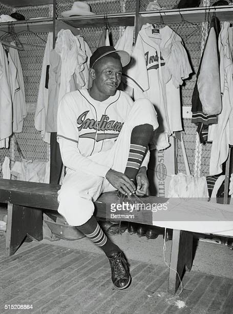 """Cleveland, Ohio: New Indian Hurler. Decked out in a Cleveland Indians uniform, Leroy """"Satchel"""" Paige smiles as he ties his shoelace in the dressing..."""