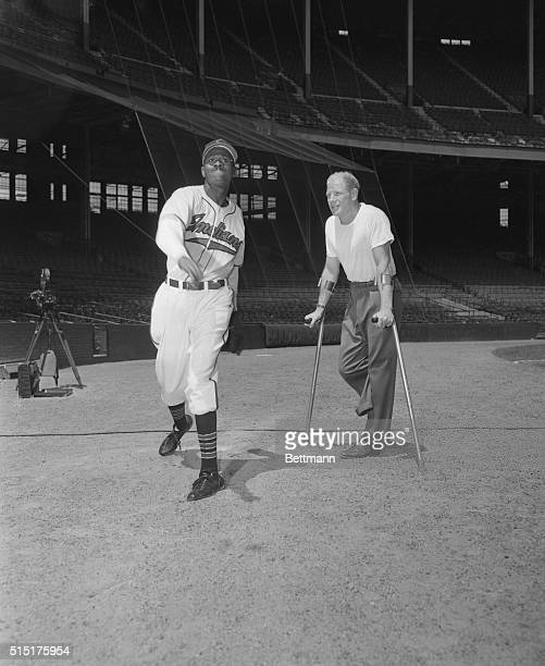 """Cleveland, Ohio: Showing Veech How Its Done. """"satchel"""" Paige demonstrated his pitching arm to Bill Veeck, Cleveland Indians president, during a..."""