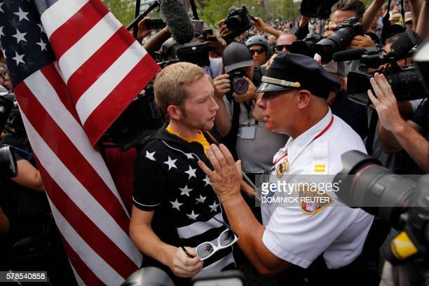 Cleveland police officer speaks with a protester on Cleveland Public Square on the final day of the Republican National Convention on July 21 in...