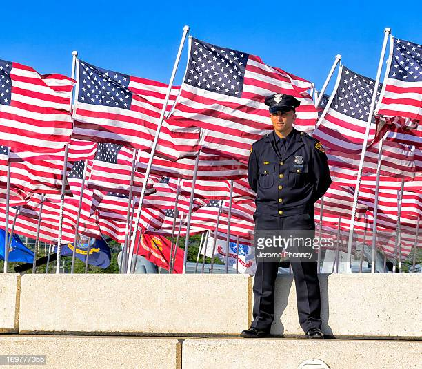 Cleveland Police Officer stands Tall in front a field of United States Flags during Marine Week Cleveland.