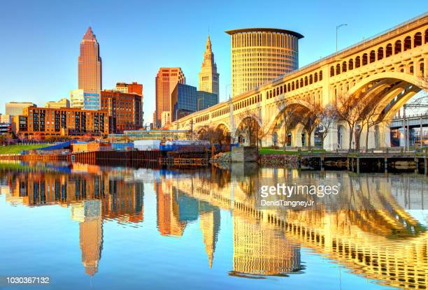 cleveland skyline reflecting on the cuyahoga river - cleveland ohio stock photos and pictures