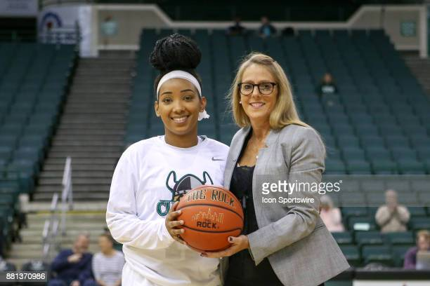 Cleveland State Vikings guard Khayla Livingston is presented with the game ball from the game in which she scored her 1000th career point by...