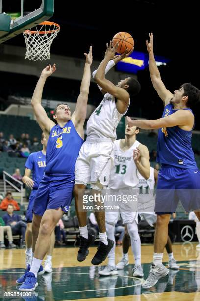 Cleveland State Vikings Kenny Carpenter shoots as Notre Dame College Falcons forward Oliver Megins and Notre Dame College Falcons forward Angelo...