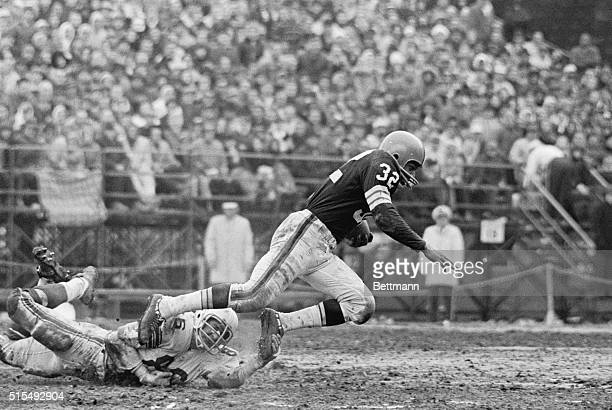 Cleveland's Jim Brown is tripped up by Cards' Don Brumm after four yards gain on pass from Frank Ryan in third quarter of CardsBrown game Brown was...