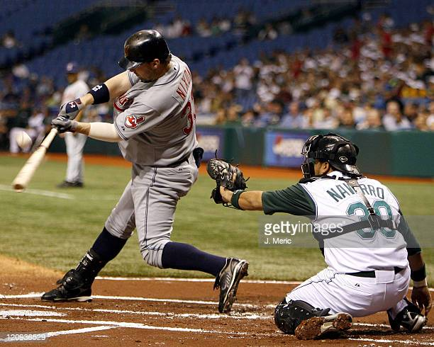 Cleveland's Trot Nixon makes contact as Tampa Bay's Dioner Navarro waits for the ball during Friday night's game at Tropicana Field in St Petersburg...