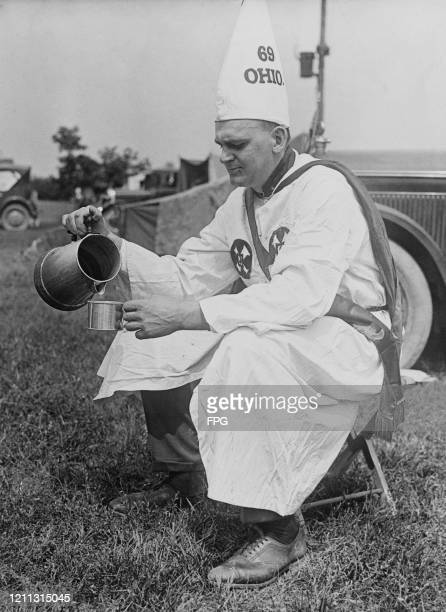 Cleverly, a member of the Ku Klux Klan from Ashtabula, Ohio, refreshing himself with a cup of coffee before participating in a Ku Klux Klan parade in...