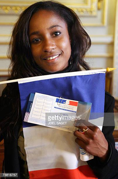 A young woman poses with her electoral card a French and an European flag after receiving them during a ceremony at the city hall of ClichylaGarenne...