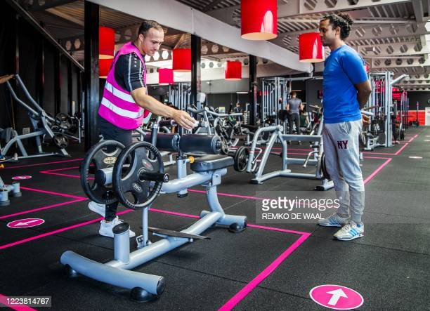 Client and a staff member stand in a gym with workout machines placed apart from each other to keep social distancing measures after fitness centres...