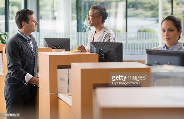 client and bank employee talking by counter - cashier stock pictures, royalty-free photos & images