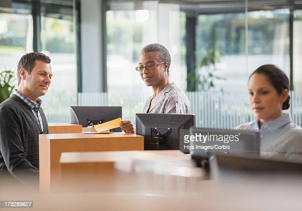 Client and bank employee talking by counter