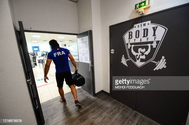 A client arrives at the Body Staff Gym fitness centre on the day of the reopening of the gym on June 2 in ArtiguespresBordeaux southwestern France as...