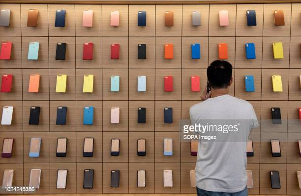 A client looks at a wall fully occupied with colorful iphone cases at the American multinational technology company Apple store in Causeway bay Hong...