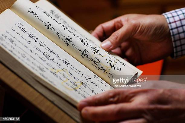 A client looks through a Japanese song book at Yuko Asakusa's home studio in the Asakusa District on November 6 2014 in Tokyo Japan 91 year old Yuko...