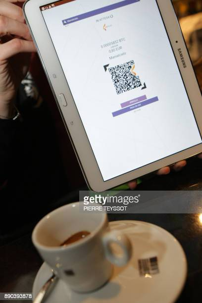 A client of the bar 'Mani Al Cielo' pays his coffee with bitcoins on December 11 2017 in Rovereto northern Italy Bitcoin surged past $18000 after...