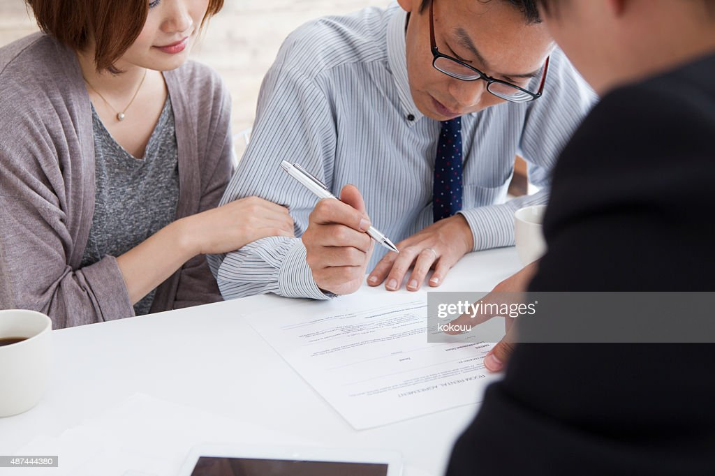Client signing a real estate contract in real estate agency : Stock Photo