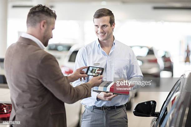 Client taking cell phone picture at car dealership