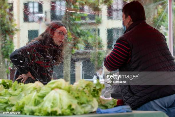 Client talks to a saleswoman at a stall protected by a plastic film in an outdoor market on May 16, 2020 in Irun, Spain. Some parts of Spain have...