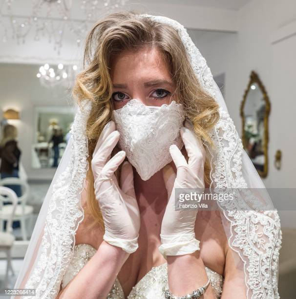 A client tries on a wedding dress together with the mask created by the designer Mariella Gennarino in the atelier in Catania open again to the...