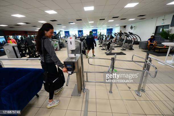 A client uses an access card to enter the Body Staff Gym fitness centre on the day of the reopening of the gym on June 2 in ArtiguespresBordeaux...