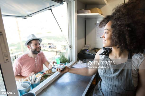 Client using credit card for payment in food van