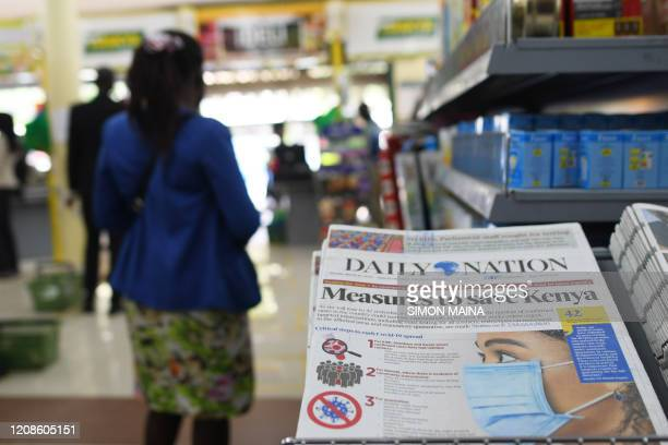 A client walks past a Daily Nation newspaper with a headline regarding the COVID19 coronavirus at a supermarket as customers stock their homes amid...