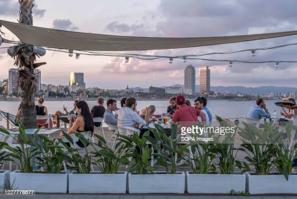 Clients are seen sitting on one of the terraces on the Barceloneta beach. After opening to the public, discotheques, dance halls, and shows have been...