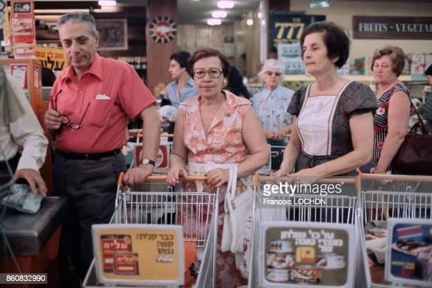Clients avec leurs chariots de courses dans un supermarché à la caisse en mai 1977 en Israël