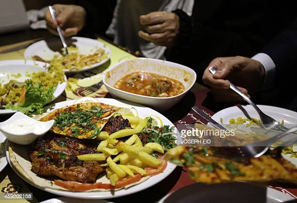 Clients eat lunch at a Syrian restaurant from Aleppo in the Lebanese capital Beirut on October 31 2014 War in Syria has brought to Beirut a wealth of...