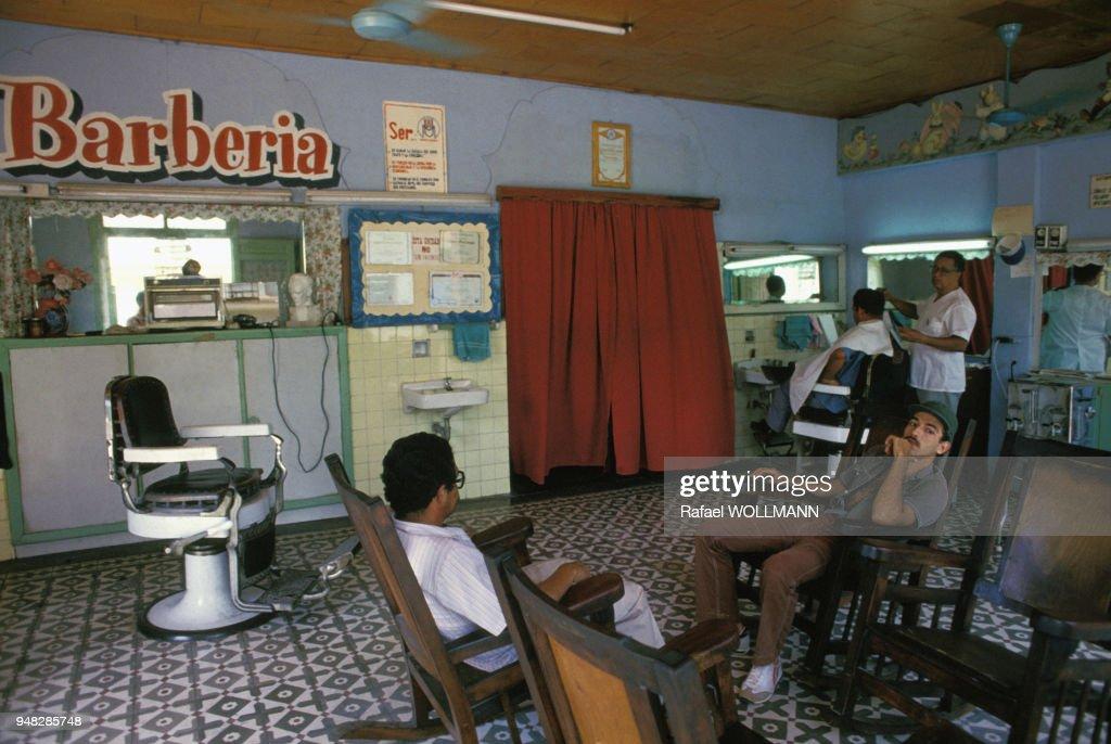 Clients et coiffeur dans un salon de coiffure pour hommes en ...