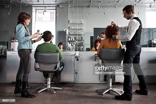 clients getting haircuts in salon - hair salon stock pictures, royalty-free photos & images