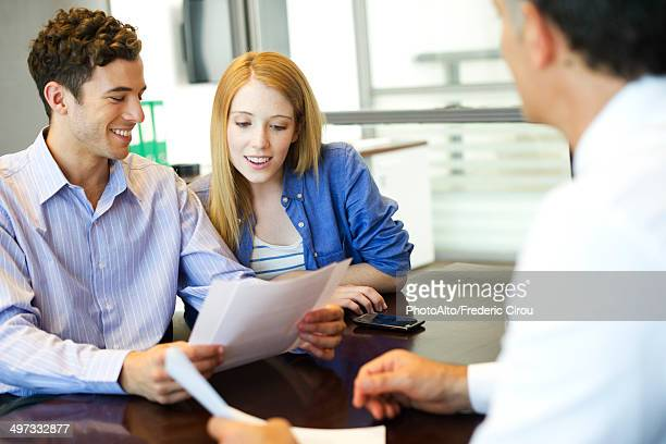 Clients going over paperwork with consultant