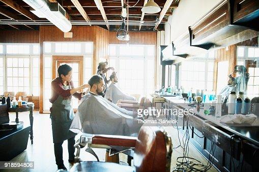 Clients having their hair cut in barber shop