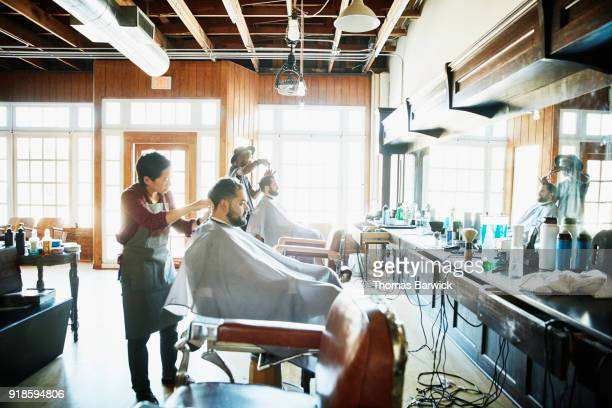 Clients having their hair cut in barber shop