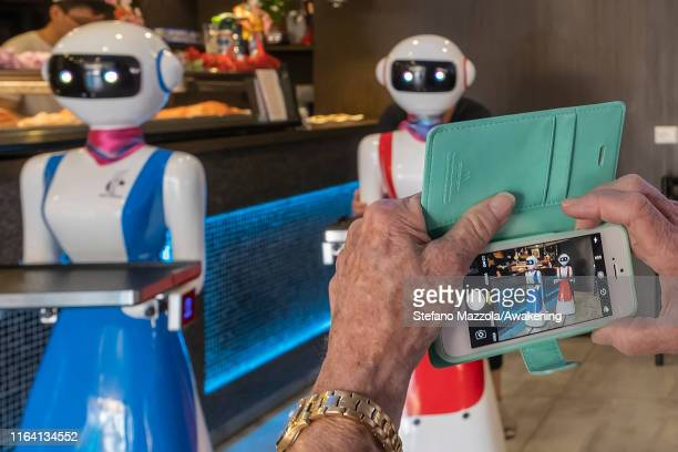 Clients take pictures of the robot waiter on July 25 2019 in Rapallo Italy The Gran Caffè Rapallo restaurant in Liguria is the first restaurant in...