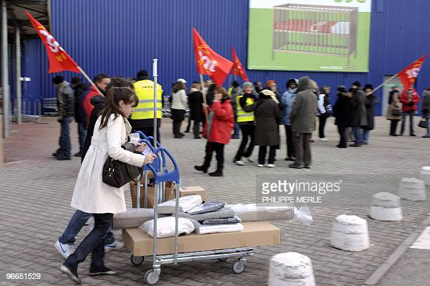 Clients walk past strikers at the Ikea store of SaintPriest near Lyon on February 13 during a national strike by Swedish furniture designer Ikea's...