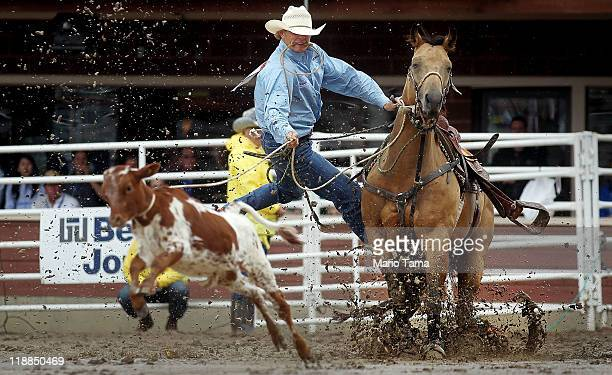 Clif Cooper leaps off his horse while chasing down a calf during the tiedown roping competition in the rodeo at the Calgary Stampede on July 11 2011...