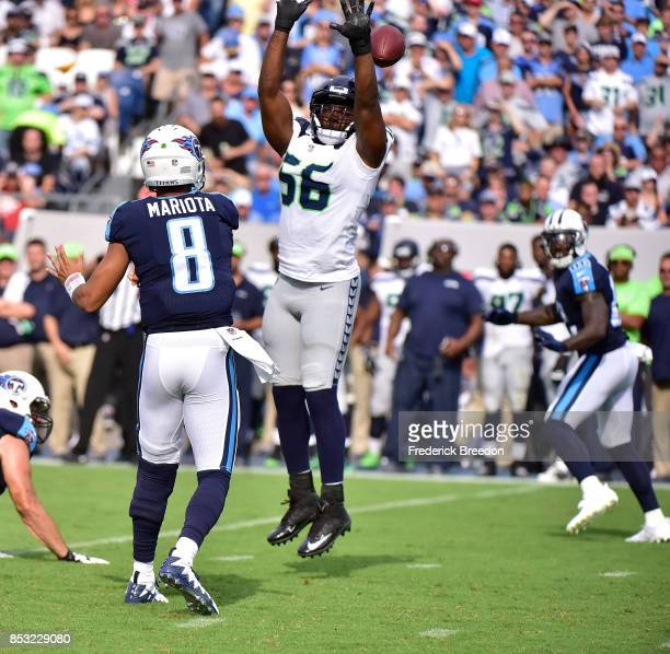 Cliff Avril of the Seattle Seahawks jumps while attempting to block a pass by quarterback Marcus Mariota of the Tennessee Titans during the first...