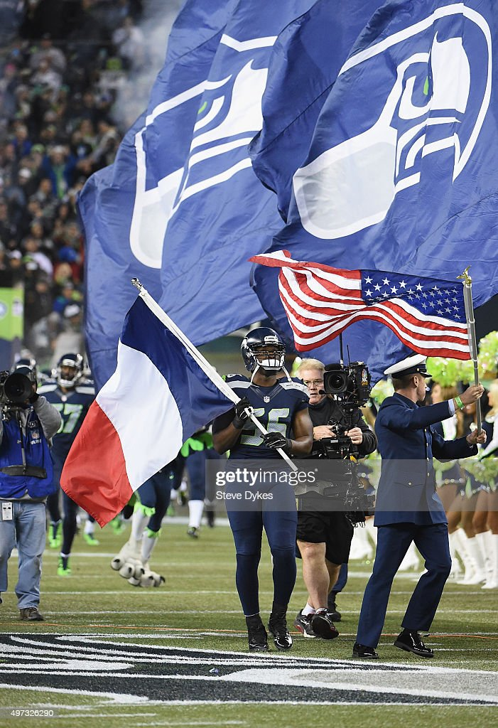 Cliff Avril #56 of the Seattle Seahawks walks onto the field with a French flag in honor of the victims of the recent terrorist attacks in Paris prior to the game between the Seattle Seahawks and the Arizona Cardinals at CenturyLink Field on November 15, 2015 in Seattle, Washington.