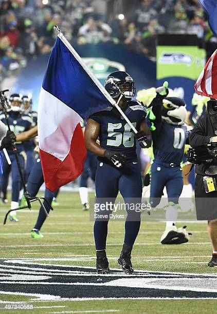 Cliff Avril of the Seattle Seahawks walks onto the field with a French flag in honor of the victims of the recent terrorist attacks in Paris prior to...