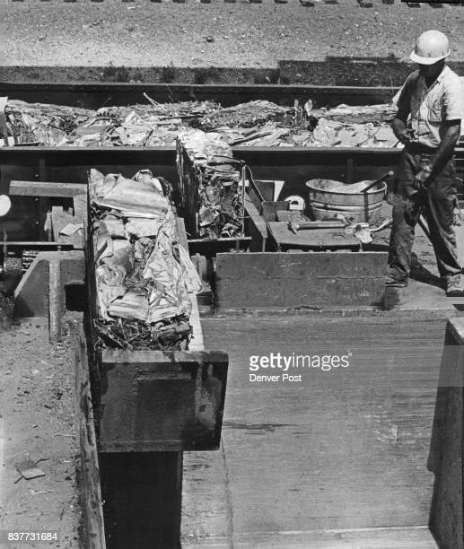Cliff Beatty 4027 S Santa Fe Drive hopper tender for the metal baler gets ready to make a final check of the compressed steel block for any...