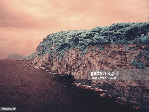 cliff by sea against cloudy sky - david cliff stock pictures, royalty-free photos & images