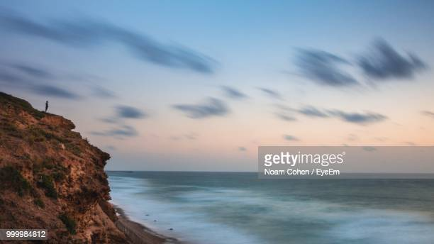 Cliff By Sea Against Sky During Sunset