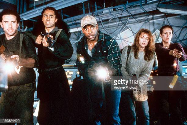 Cliff Curtis William Baldwin Jamie Lee Curtis Joanna Pacula and other crew members hold guns and flashlights in a scene from the film 'Virus' 1999