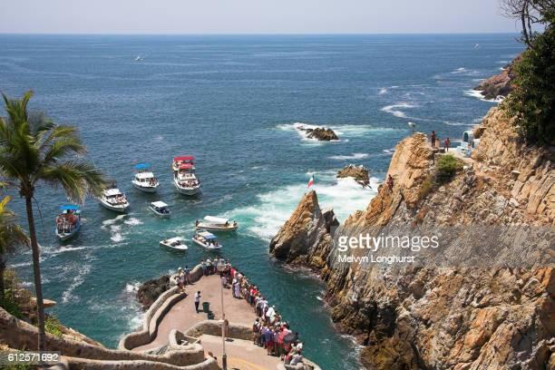 cliff divers, clavadistas, waiting to dive off the cliffs at la quebrada, acapulco, guerrero state, mexico - acapulco foto e immagini stock