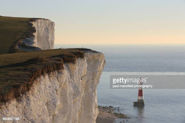 cliff edge and beachy head lighthouse - beachy head stock photos and pictures