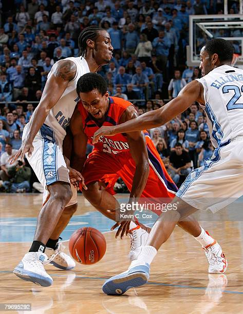 Cliff Hammonds of the Clemson Tigers loses the ball as he drives between Quentin Thomas and Wayne Ellington of the North Carolina Tar Heels during...